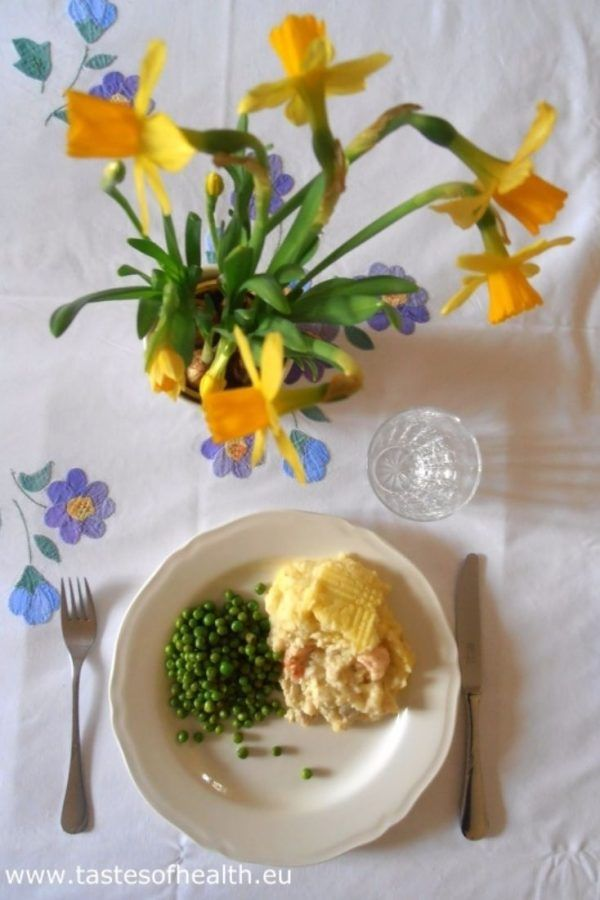 An image of Fish Pie with Prawns in a serving dish with green peas, plate, cutlery and a blooming daffodils on a tablecloth.
