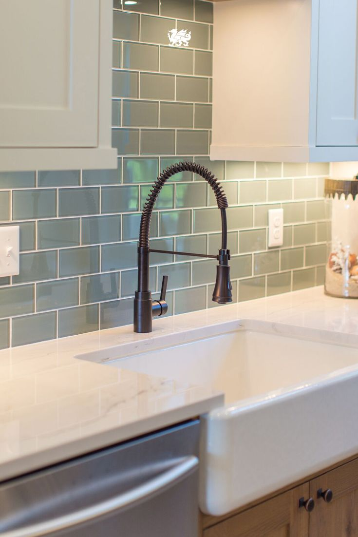 A sea green backsplash accentuates the farmhouse sink and Ella™ marble quartz countertop in this gorgeous kitchen revamp by @JKathDesignBuil