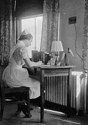 Organize your genealogy - Student nurse Eileen Larson Johnson writing a letter home in 'C' floor dorm room, Alpha Dorm, Swedish Hospital School of Nursing, Minneapolis, 1939.  MHS Collections, Location no. R2.2 p75 Negative no. 31562