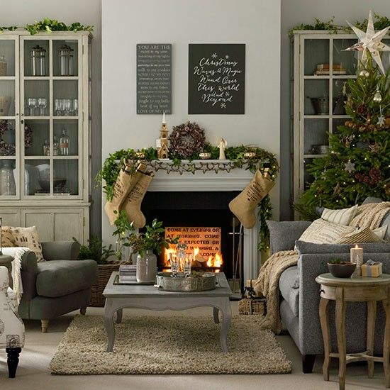 The fireplace is the focal point of this festive living room, with the mantelpiece decorated with a garland and stockings
