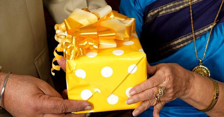 """Sugerencias de regalos creativos para un aniversario número 50 de bodas. El 50 aniversario de bodas tiene la etiqueta ser las """"Bodas de Oro"""", siendo el """"oro"""", el tema clásico. Si estás preparando un aniversario de bodas número 50 para una pareja o estas comprando un regalo para su aniversario, ellos apreciarán tu creatividad y consideración."""