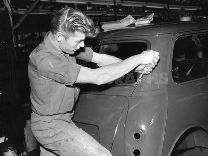 David Bowie on the BMC Mark-I MINI assembly line, some time in the mid-1960s. Photo credit MOTORGRAPHS and classic1275cc.tumblr.com