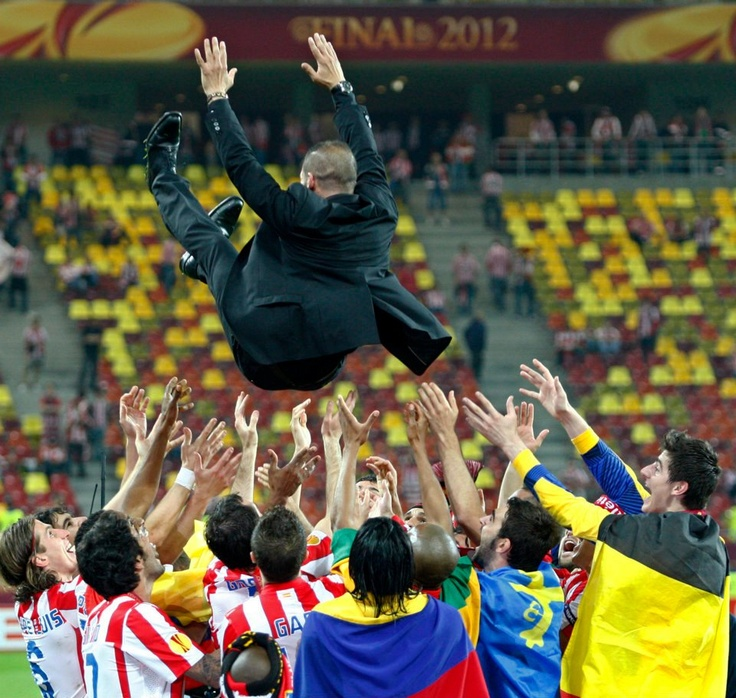 The players celebrate by throwing El Cholo in the air.