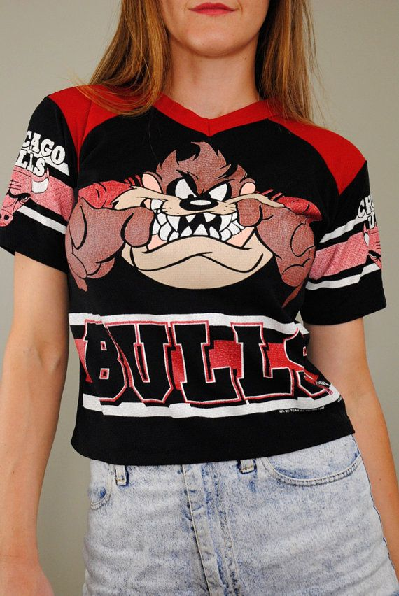 Vintage Chicago Bulls jersey from the 90s. Its made of mesh polyester in red and black. The front is screen printed with Taz from Looney Tunes, and the sleeves are printed with stripes and the bull logo. This shirt has a v- neck, short sleeves, and it slips over the head with no closures. Label: Bull Frog  Fabric: not marked, feels like polyester  Excellent vintage condition      .............................  Measurements   This shirt best fits a small. Please check the measurements to…