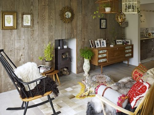 Walls clad in reclaimed wood paired with a wood burning stove.