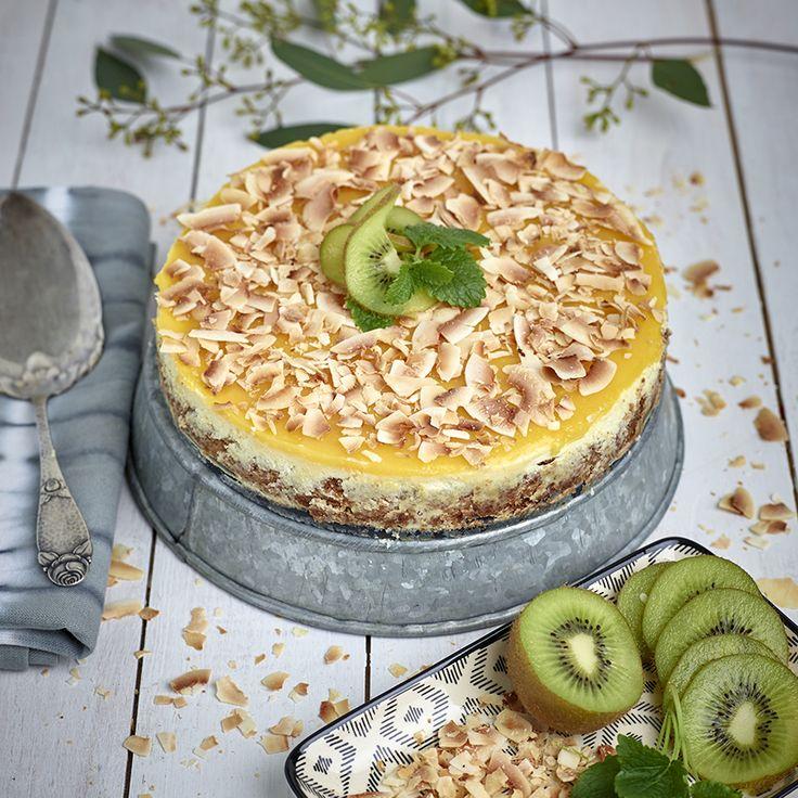 Cheesecake med smak av kokos och mango, med hyvlad kokos på toppen.