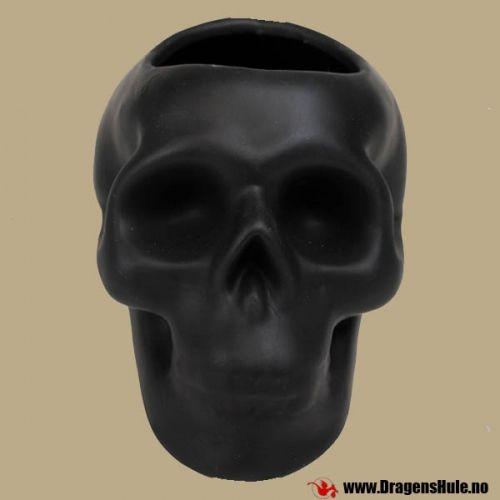En stilisert hodeskalle med hull i toppen til å ha penner eller hva det måtte være i.Materiale:matt svart keramikk. Mål: ca 9cm høy, 8 cm bred og 13 cm lang.