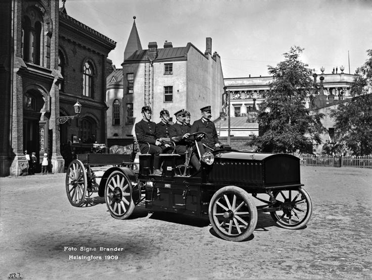 Sähköauto vuodelta 1909 Pääpaloaseman pihalla, osoitteessa Korkeavuorenkatu 26. Kuljettajana koneenkäyttäjä Flink ja vieressä ruiskumestari Leskinen.  Foto: Signe Brander, 1909.