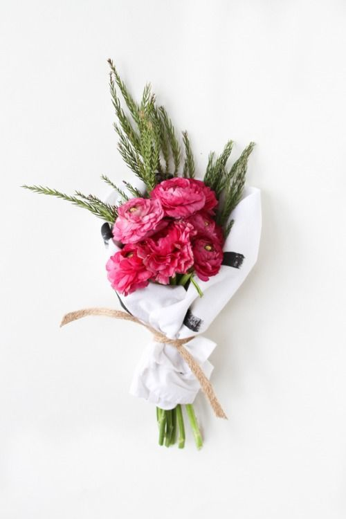 A simple but sweet bouquet of bright pink fuchsia blooms with a little foliage tucked inside and wrapped in paper in a ribbon. That's a gift waiting to happen.