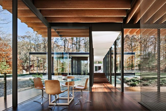 The roof over the glass-enclosed walkway linking the new living space and the mid-century piece appears to have been slid below the canopies that surround both structures.