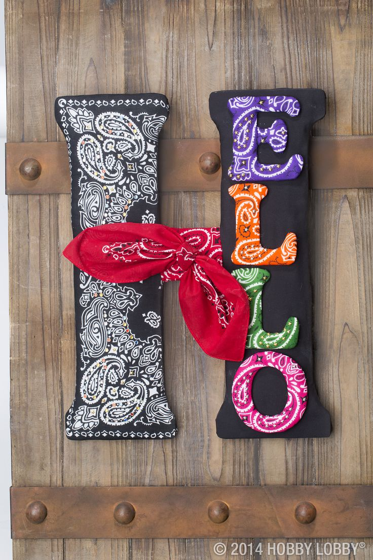 "This DIY is a fancy way to say ""howdy""! Drape a big ol' wooden letter with bandanas. We glued quilt batting to the wood, then wrapped the fabric tightly, gluing it at the back. Finally, we added a handful of gold and gemstone grommets for a touch of bling. Yee-haw!"
