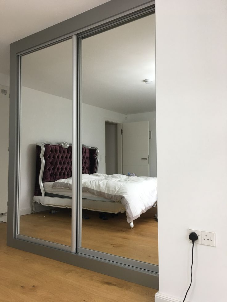 another room with fitted sliding wardrobes finished in a brushed aluminium.