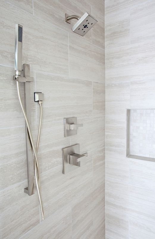 Beautiful shower by Jennifer Reynolds Interiors. Custom shower niche with handheld spa showerhead. Marble vein-cut slab, Brizo fixtures.