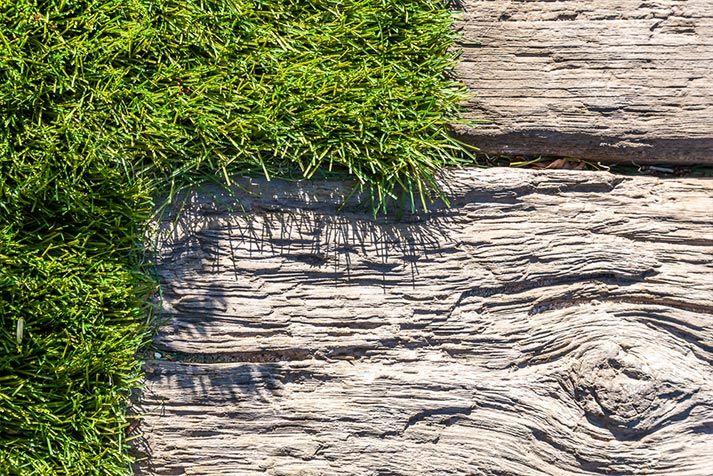 Een onderhoudsvriendelijke tuin waar slim gebruik is gemaakt van materialen. En ook al kijkt u een tijdje naar de bielzen die het pad vormen; het is nauwelijks opmerkbaar. Het zijn geen bielzen, maar schitterende driftwood tegels van Timberstone. Ook het gras is geen echt gras, kunstgras. Hout kan verweren, gras moet bijgehouden worden. Kortom: welkom in de onderhoudsvrije tuin.