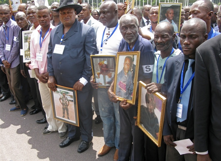 Relatives hold images of departed loved ones at a memorial service for victims of a huge munitions blast on 4 March 2012 in Brazzaville