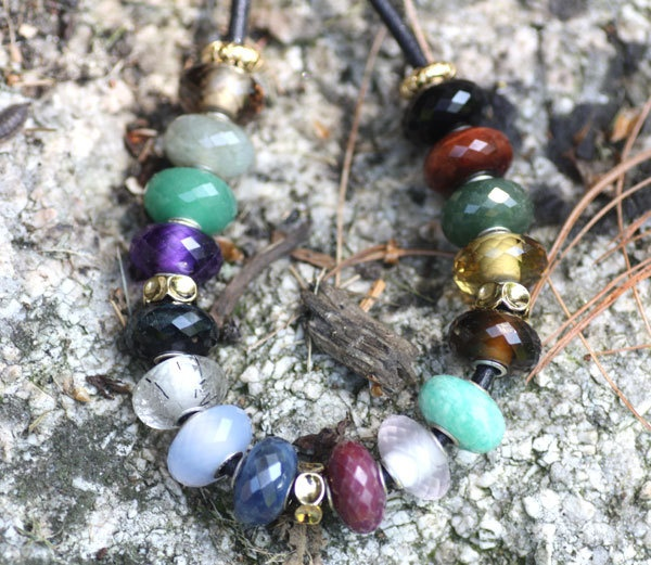 Trollbeads faceted stones on stone wall.