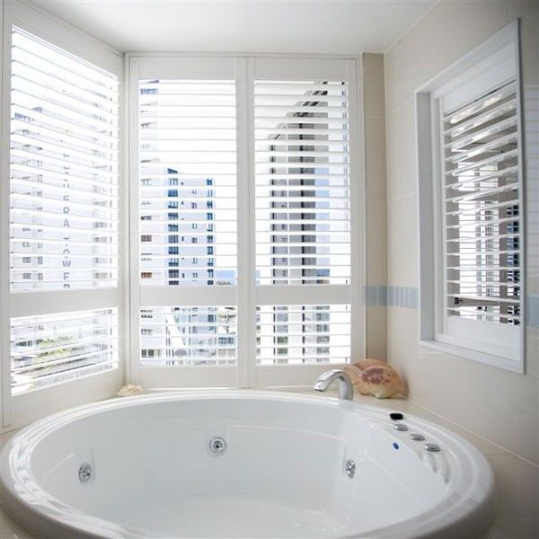 Rounded Bath With Gorgeous White Window Shutters.