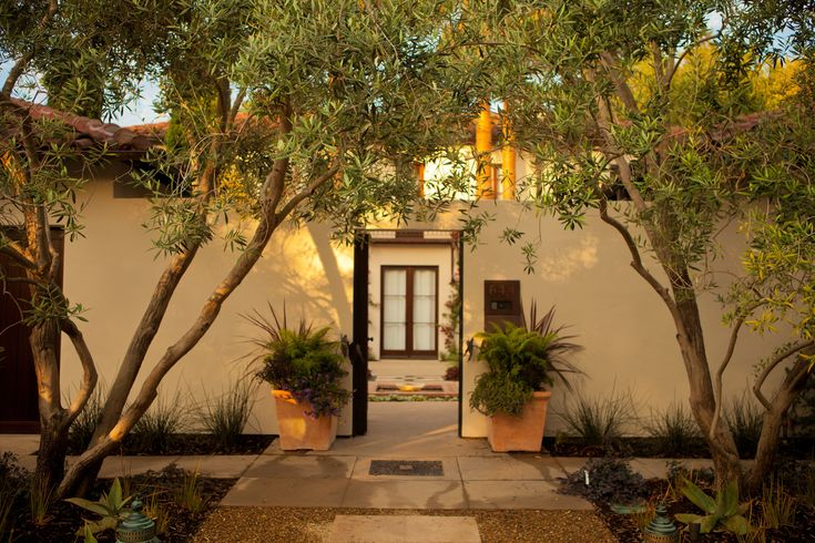 Spanish style home with tall courtyard wall flush to garage.