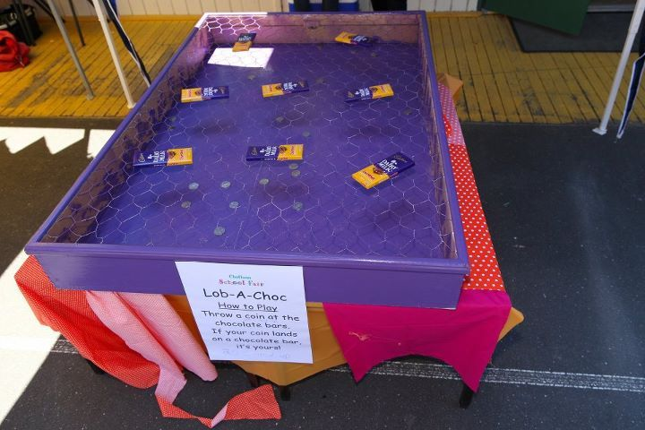 Lob a choc. Blocks of chocolate sit on chicken wire covering a box. Players throw coins at the chocolate, if their coin lands on a block they win it. If not the coins fall through the chicken wire into the box below. A great money spinner!
