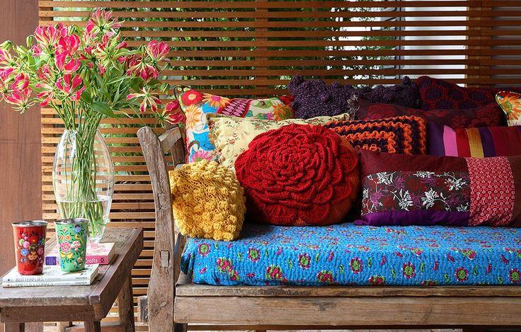 As cores das almofadas, algumas de crochê, combinam com a colcha que envolve o assento do banco. Assim, o conjunto fica harmônico
