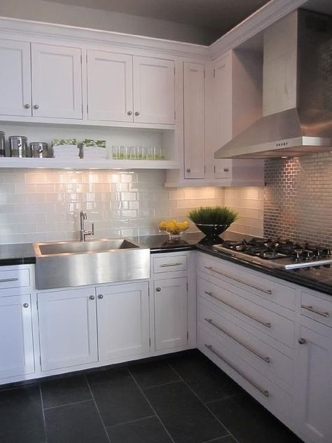 White kitchen from Shelter Interior Design blog - white shaker cabinets, dark countertops, white subway tile backsplash, grey tiles behind range, dark slate or tile floor