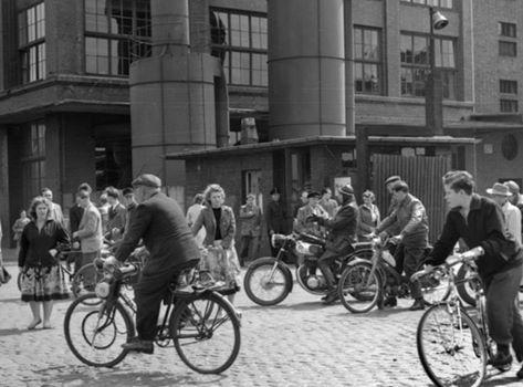 Schichtwechsel bei Conti (Continental AG) in Hannover, Vahrenwalder Straße. Arbeiter verlassen auf Zweirädern unterschiedlicher Bauart das Werksgelände. Foto von Wilhelm Hauschild, 1958.