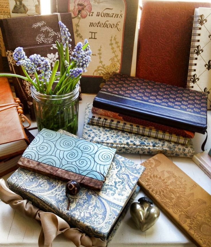 a collection of my journals displayed with my trinkets and cut muscari and and set on my windowsill