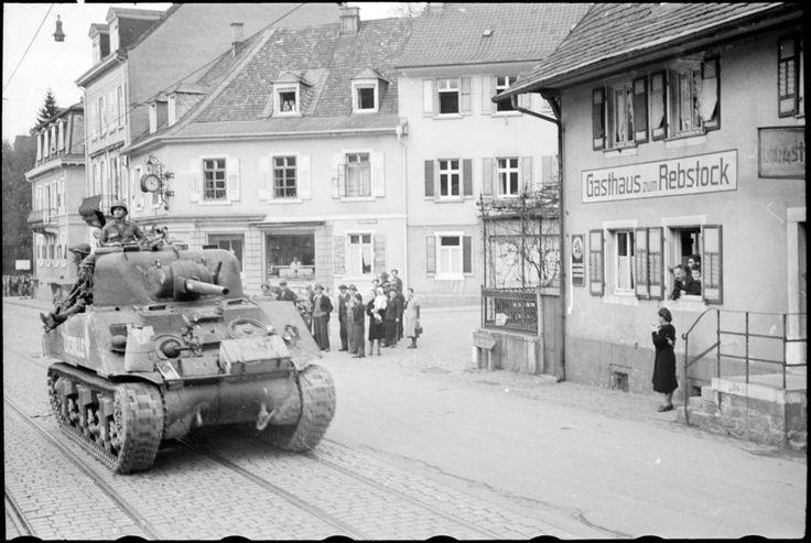 Prise de Baden-Baden – Entrée des Français dans la ville.Baden-Baden est prise le 12 avril 1945 par le 5e RCA (Régiment de Chasseurs d'Afrique) de la 1re DB (Division Blindée), à la suite d'un mouvement tournant opéré dans la montagne qui a permis d'éviter Rastatt où les troupes allemandes ont établi une ligne de résistance importante. Baden-Baden n'a pas été éprouvé par la guerre.  Dans les rues de la ville, la population allemande assiste au passage des blindés français.