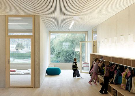 Huge round cushions in shades of mustard yellow and cornflower blue add colour to the pale concrete and timber interior of this kindergarten in western Austria by local studio Bernardo Bader Architects.