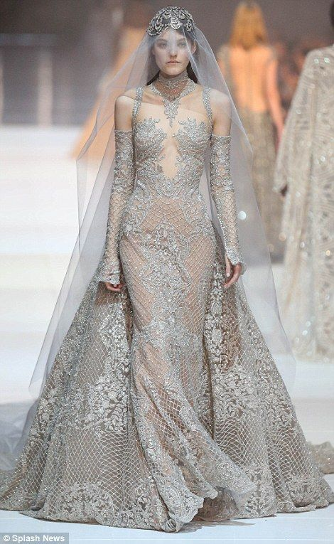 Dramatic: Another wore a heavily embellished silver gown with strategically placed sequins, beading, beautiful off-the-shoulder long sleeves and a beaded capped veil which cascaded down her back