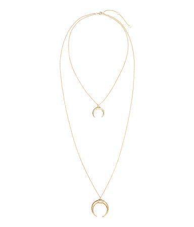 Gold-colored. Narrow, double-strand metal chain necklace with a pendant. Adjustable length, 14 1/2 - 17 in.
