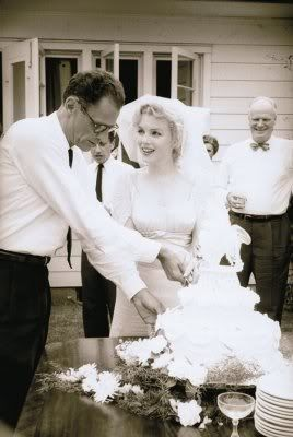 Marilyn Monroe married third husband, Arthur Miller in White Plains, New York on June 29, 1956 in a secret civil ceremony. She wore a plain sweater and skirt and no hat. However, in the photos of the happy couple celebrating and sharing wedding cake, after their traditional Jewish ceremony on July 1, she wore an elegant empire line dress featuring elbow length sleeves and a ruched bodice. Marilyn complemented the dress with a full shoulder length veil, attached to a subtle white skull cap.