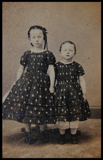 Both of these girls are deceased. They are posed on stands to appear life like. If you look at their feet you can see the bottom of the stands....