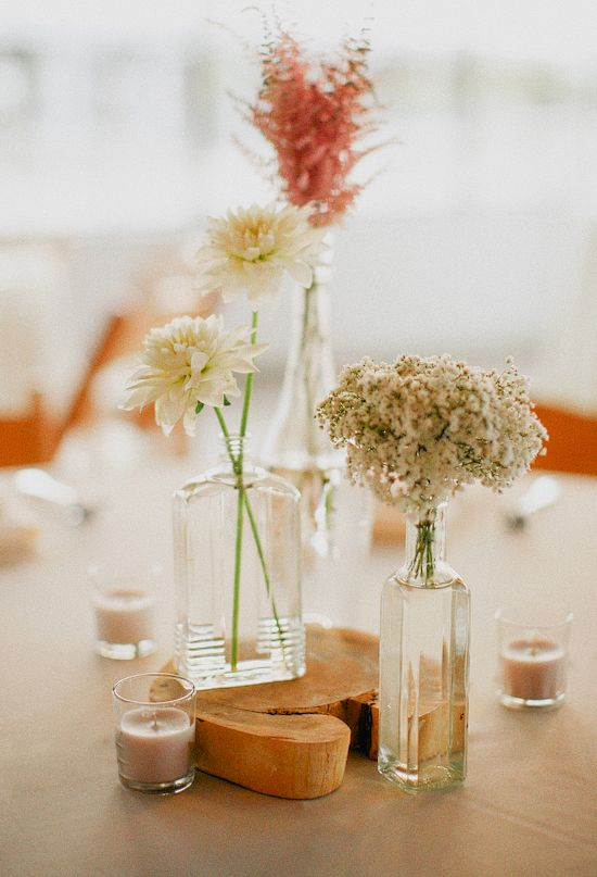 unique (mismatched) bottle bud vases....these at each end of a long table, with a larger centerpiece in the middle of the long table....
