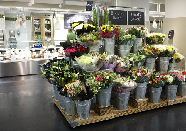 All change: The plastic flower displays have been thrown out and replaced with galvanised steel buckets placed on wooden shelves.