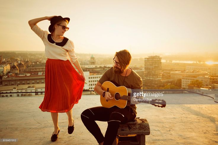 the guitarist playing the guitar and the woman dancing,nice sunny day,on top of the city on a roof