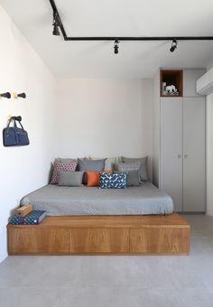 """A cama, por exemplo, além de fazer as vezes do sofá, como é comum em apês pequenos, tem gaveteiros por toda sua volta que podem ser usados para guardar roupas de cama e banho. Já no lugar do estrado as arquitetas esconderam um alçapão, no qual é possível guardar até dois colchões extras para as visitas - ou qualquer outro item que pareça mais essencial!  Ainda é possível encontrar """"armários secretos"""" na cozinha, na sala, no banheiro e na pequena sala de TV, feita no lugar da varanda. Atrás…"""