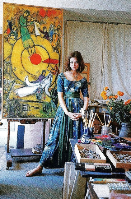 Ivy Nicholson wearing dress by Claire McCardell is standing in front of Marc Chagall's painting Le Soleil Rouge in his studio in Vence, photo by Mark Shaw, 1955