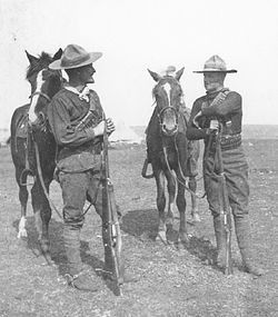 Two dismounted troopers from the 1st Battalion, Canadian Mounted Rifles in conversation on the South African veldt, their Stetsons showing signs of wear. Their dress is adapted to the conditions of service on the veldt and shows the Western-Canadian influence.