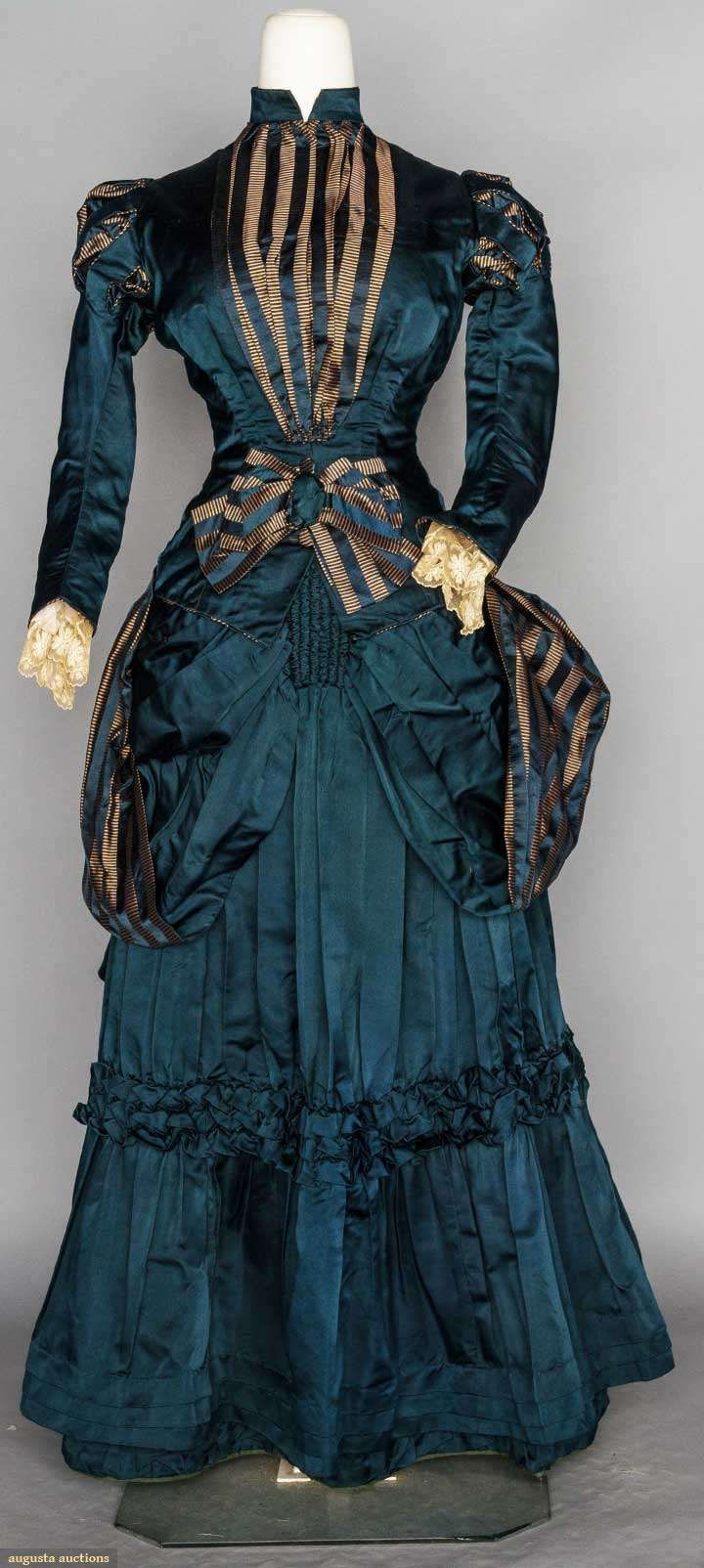 YOUNG LADY'S BUSTLE DRESS, 1880's, 1-piece navy silk satin, bodice & bustle skirt trimmed w/ navy & copper striped ribbon | Augusta Auctions