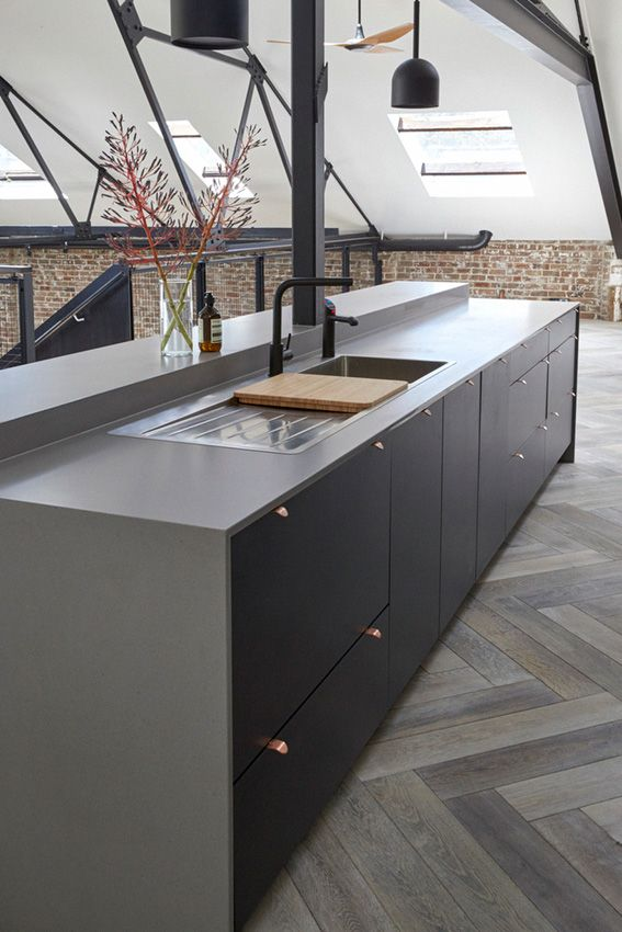 Award Winning Kitchen Design - sydneykitchens.com.au Contemporary and classic open plan kitchen using white, black and grey palette. Matt black cabinetry, black veined marble splashback, industrial style Caesarstone benchtop. Copper and gold accents, copper handles, black hanging pendants, brickwork and timber herringbone flooring.