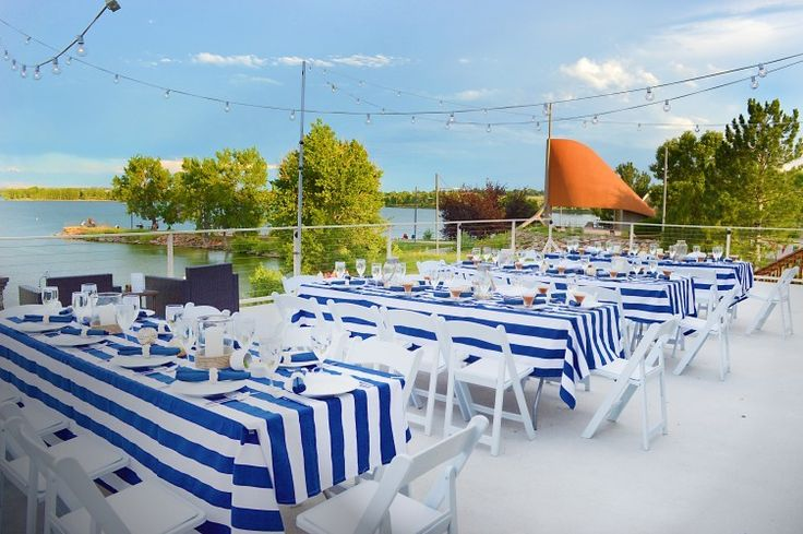 As the only beach wedding venue in Denver, the Lake House at Cherry Creek offers both mountain and waterfront views to set the scene for a gorgeous wedding. Pictured here, a nautical outdoor wedding reception featuring picnic tables covered in navy striped table cloths and simple strings lights. It doesn't take much decor to make a patio party on the lake look incredible. | The Lake House at Cherry Creek - Colorado wedding venues