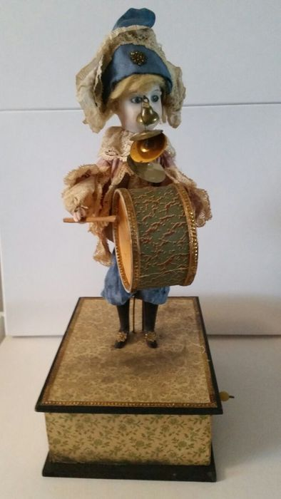 """Size with box: ca. 36 cm Biscuit porcelain head, numbered with """"2"""" on the back of the head, solid blue eyes, closed mouth, original clothing with lace, Clamp on head cover, wooden legs. When the crank is turn, the melody of """"alle Vögel sind schon da"""" sounds and hand and head move. Factory Fund; Germany"""