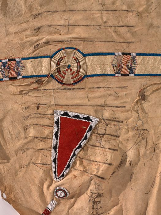 Apsáalooke warrior's exploit robe (detail), ca. 1850. Fort Benton, Montana. Buffalo hide, pigment, red wool trade cloth, beads, porcupine quill, horsehair; 224 x 193 cm. Collected by William H. Schieffelin. Presented by William de la Montagne Cary. 1/2558