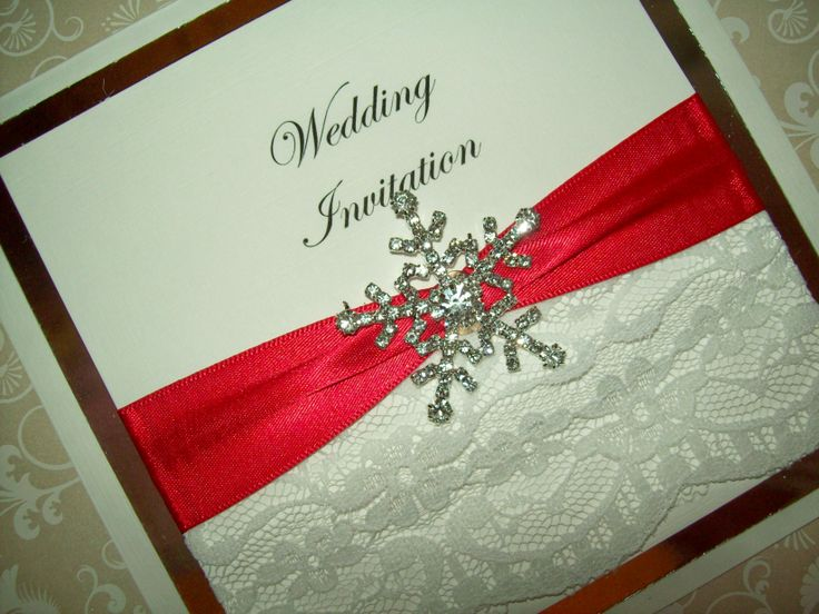 A beautiful diamante snowflake wedding invitation with lace, satin ribbon and a silver or gold frame, perfect for winter or christmas weddings