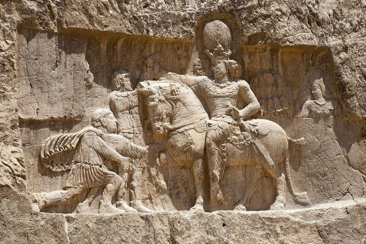The triumph of Shapur I (r. 241-272). This Sassanid rock relief depicts Shapur's victory over two Roman emperors, Valerian and Philip the Arab. This is presented at Naqsh-e Rustam, where Shapur is represented on horseback wearing royal armour and crown. Before him kneels Philip the Arab, in Roman dress, asking for grace. In his right hand the king grasps the uplifted arms of what may be Valerian; one of his hands is hidden in his sleeve as the sign of submission.