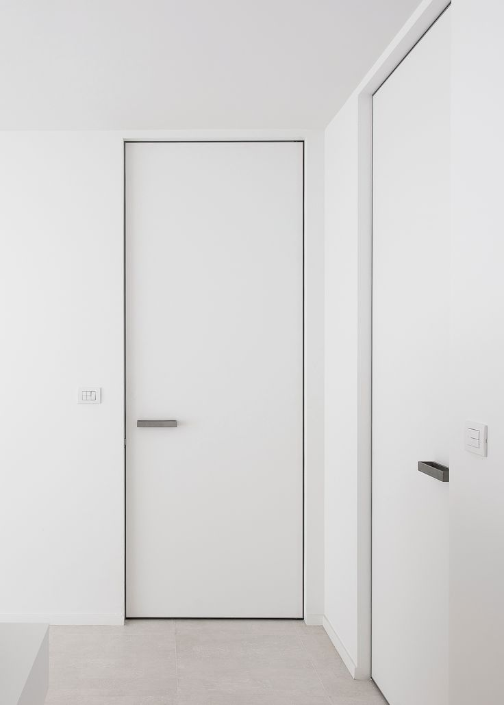 Invisible interior doors, custom-made with a invisible aluminium door frame. The frame is positioned before the wall finish and both frame and door panel are fully custom-made.
