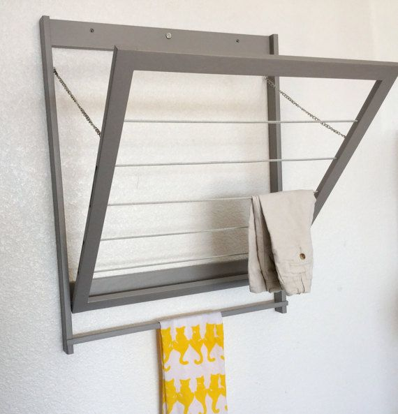 A new twist on a must have for your laundry or mudroom. Modern drying rack is constructed with solid wood frame and vinyl coated steel cable, making it