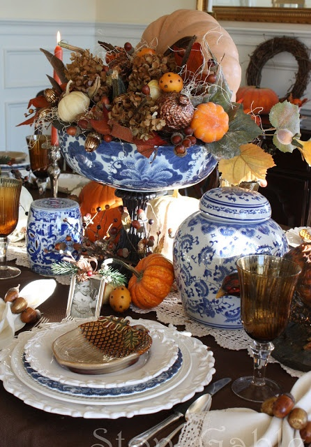 A traditional fall tablescape combines blue & white porcelain with pumpkins, pine cones & oranges.