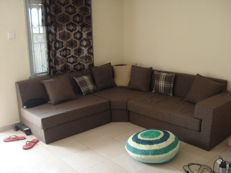 Coffee Brown Meets Mint. Coffee brown corner sofa, Burberry inspired Pillows, Ugandan Kitenge Curtains and Footstool made of recycled fabrics by a local social enterprise